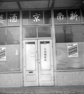 [Japanese storefront with real estate for rent signs posted on the window]
