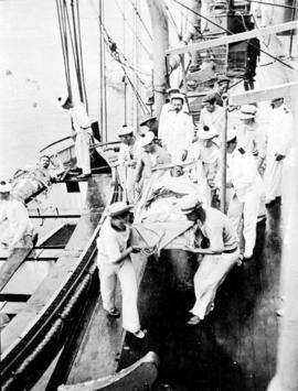 "Hoisting the ""Emden"" wounded up in lifeboats [onto the ""Empress of Russia""]"