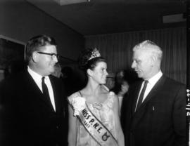 Judy Collyer, Miss P.N.E., with two men at P.N.E. event