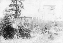 [Men with their bikes beside the first Brockton Point lighthouse]