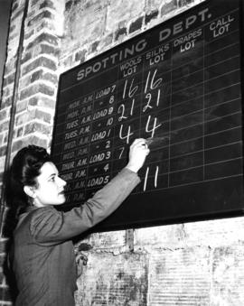 Nelson's Laundry staff member writing on the schedule board for the Spotting Department