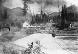 [Young man travelling across Capilano River dam in a cable car]