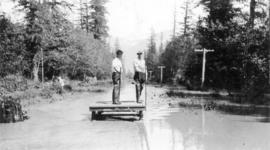 [Two men on a raft during flooding of the Fraser River]
