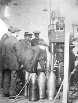 [King George inspects a hydraulic press during a visit to a munitions factory]