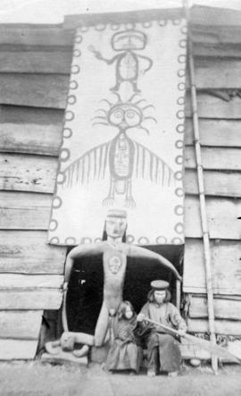 [Two unidentified First Nations people at the entrance to the lodge]