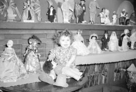 [Beverly Diane Rogers seated among part of Mrs. George R. Matthews doll collection]