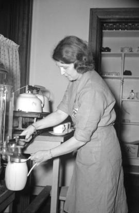 [Red Cross worker preparing refreshments at a blood donor clinic]