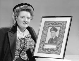 Miss Hanna Tilson [holding framed portrait of Flying Officer Henry Tilson, D.F.C.]