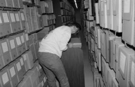 Conservator Sue Bigelow working in the stacks at the City of Vancouver Archives