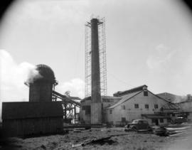 [Smoke stack surrounded with scaffolding at an industrial site]