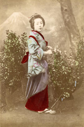 [Full-length studio portrait of woman in formal Japanese dress in front of mountain backdrop]