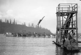 [Woman diving from tower at resort swimming area]
