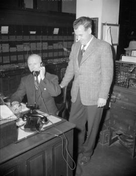 [Two men, one on the telephone, at work during the change over at the Bayview Cedar Exchange]