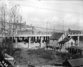 [Hastings Street viaduct, showing buildings in foreground and B.C. Sugar Refinery in the distance]