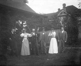 [Men and women posing with bows and arrows in front of house]
