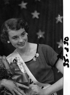 Portrait of Nancy Hansen, Miss P.N.E. 1954, posing with trophy and flowers