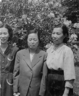 Mrs. Chan and two unidentified women in front of a rhododendron