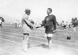 [Mayor L.D. Taylor shakes hand of athlete holding discus]