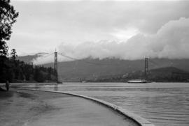 [View from the seawall of a ship passing under the Lions Gate Bridge under construction]