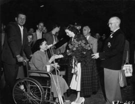 Miss P.N.E., accompanied by P.N.E. President J.S.C. Moffitt, handing flower to woman in wheelchair