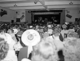 [Audience watching musicians on a stage with a Kelly's appliance display and a Mooseheart ba...