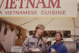 Man and woman in front of Vietnamese Cuisine stand at Food Fair during the Centennial Commission'...