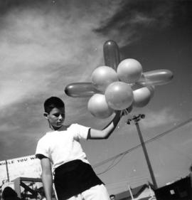 Boy holding balloons on P.N.E. grounds