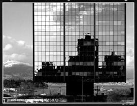 Buildings reflected in the West Coast Transmission Building, with a view of Coal Harbour