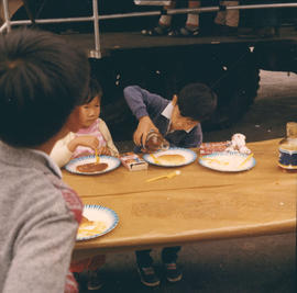 Children eating on P.N.E. grounds