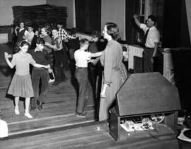 Square dancing in gym in old building, Stuart McRae, teacher