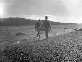 [Two men carrying oysters on the beach at] Oyster Bay