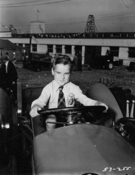 Young boy on tractor in outdoor machinery display by Livestock building