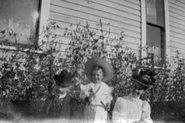 L.D.T. - T.P.T. - A.L.T. [L.D., Theodore and Annie Louise Taylor sitting in yard of their home at...