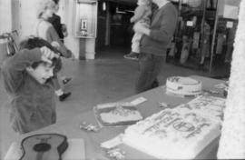 Child viewing birthday cakes on display