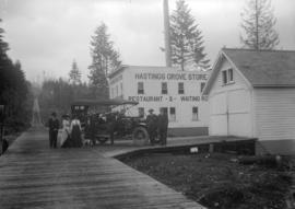 [Group of people assembled around a car in front of the Hastings Grove Store, Curtis and Duthie S...