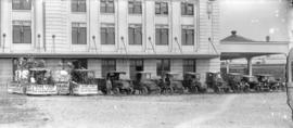 [Champion-White Ltd. fleet of trucks in front of CN Station with floats for Robin Hood Boilers an...