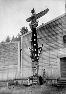 Children with Kwakwaka'wakw Totem Pole outside of Longhouse