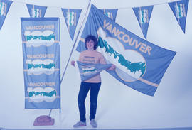 Woman posing with Vancouver Centennial promotional materials