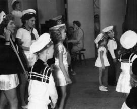 Children performing in sailor costumes on stage