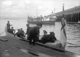 [Open boat from naval vessel with crewmen and passenger at dockside - Vancouver harbour]