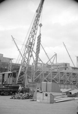 [Crane lifting heavy chains in freight area of a dock]