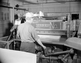 [Man cutting sheets of paper at a large machine]