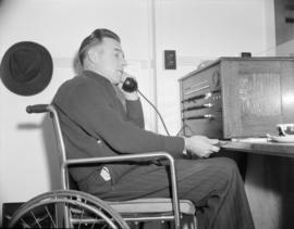 [Man in wheelchair at the Red Cross switchboard]