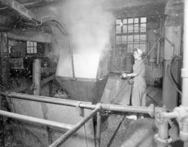 [A woman operating a machine at] Pacific Mills
