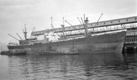 S.S. Pantanassa [at dock, with lumber-filled barges alongside]