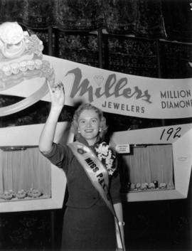 Miss P.N.E., Glenda Sjoberg, holding up ring at Millers Jewelers display in Manufacturers building