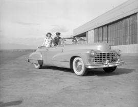 [Woman in cowgirl costume sitting in the back of a convertible with a man at the airport]
