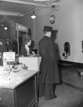 [A sailor standing beside the] Information desk [at the] Hudson Bay Company