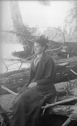 [Woman seated on driftwood on Stanley Park beach near Brockton Point]