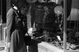 Shoppers look at jewellery and curios through storefront window
